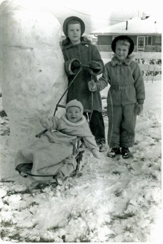 Kids next to snow phallus